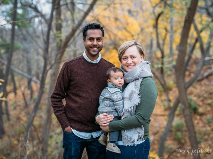 Mom and dad posing with baby in the middle in High Park in Toronto during the fall