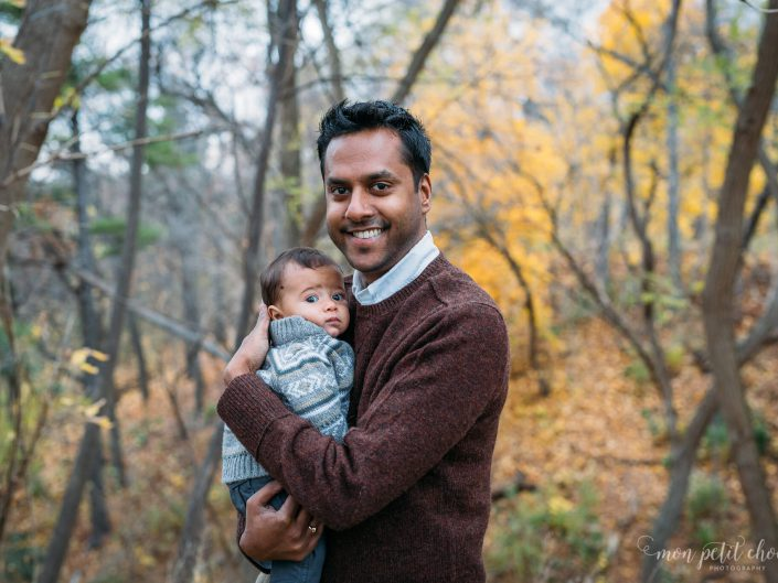 Photo of dad standing and holding baby during the fall in Toronto's High Park