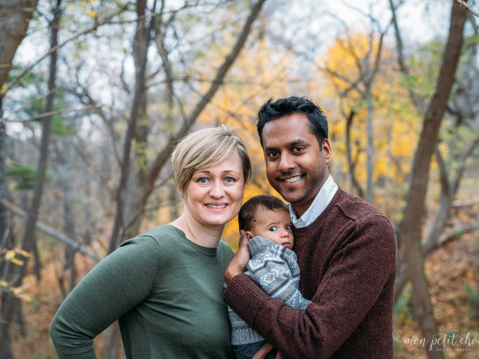 Mom and dad standing with baby in the middle, photo taken in High Park Toronto