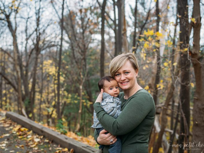 Photo taken in Toronto's High Park of mom holding baby with trees in background