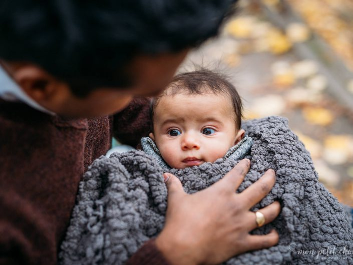 High Park fall photo in Toronto dad holding wide-eyed baby swaddled in blanket