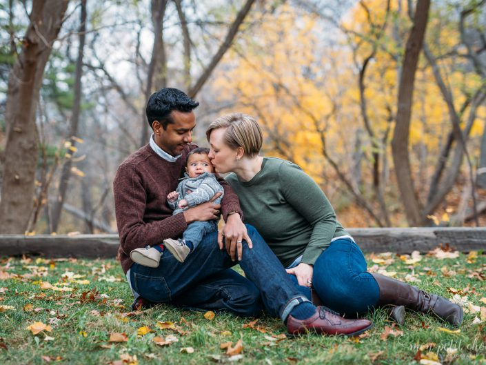 High Park fall photo with mom and dad sitting while cradling baby