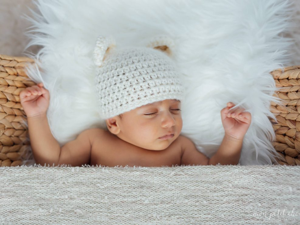 Newborn asleep in wicker basket with white hat on, photo taken in Cambridge, Ontario