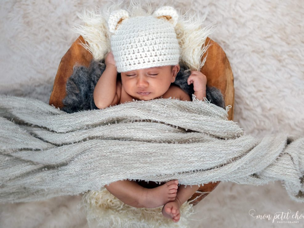 Newborn asleep in wooden basket while covered with blanket, photo taken in Cambridge, Ontario