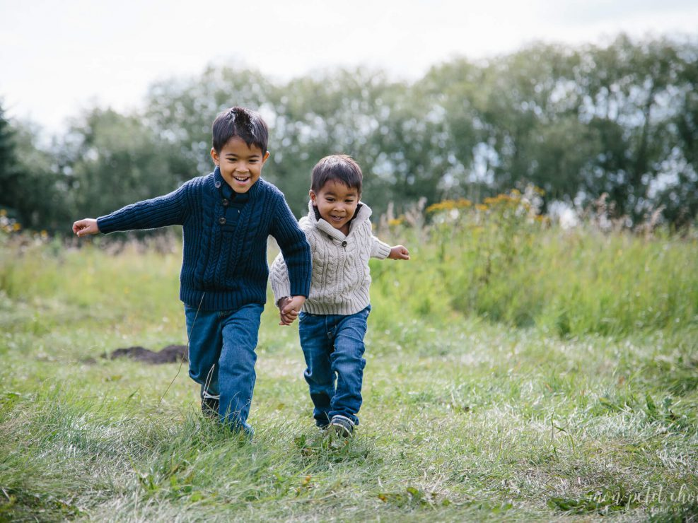 Family photo of two toddlers holding hands and running in a green field