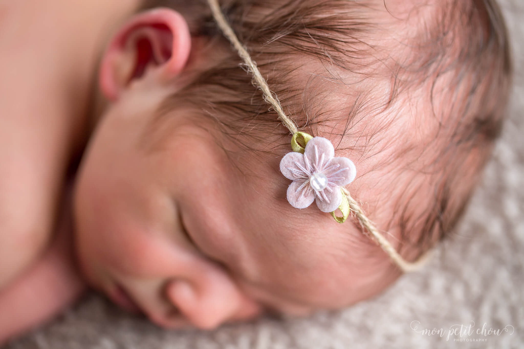Macro shot of a newborn girl wearing a decorative flower on a canvas wrap.