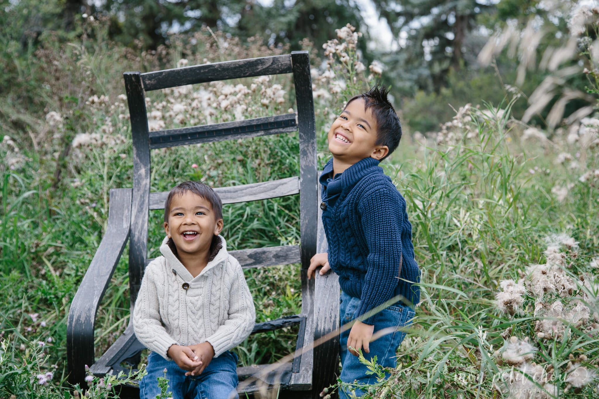 Two children laughing and sitting on prop dressed for family portrait session.