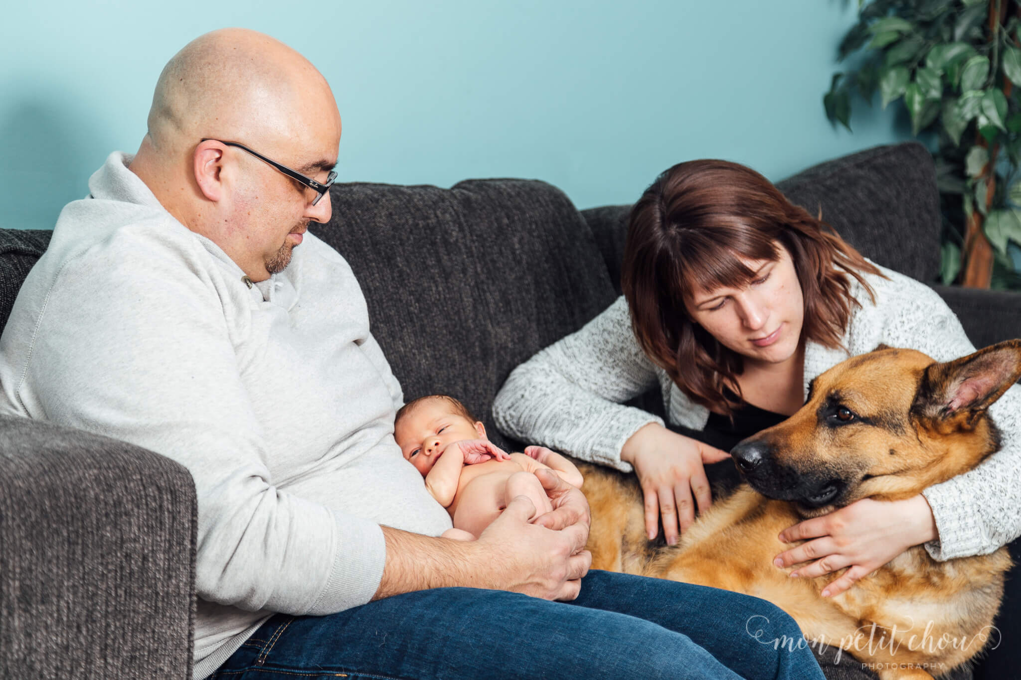 Family posed in candid moment holding baby and petting dog