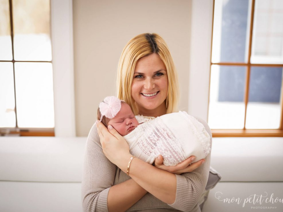 Shallow depth of field photo with mom posing with newborn is bright sunlit living room