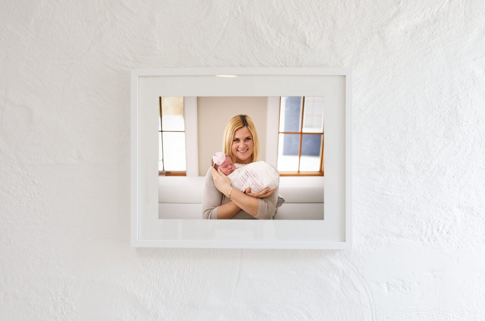 Framed photo of mom with newborn against white wall