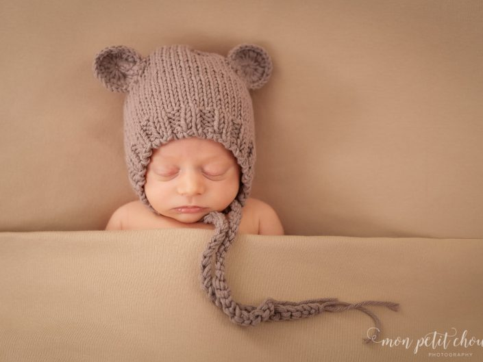 Newborn boy in a knitted bonnet with little ears.