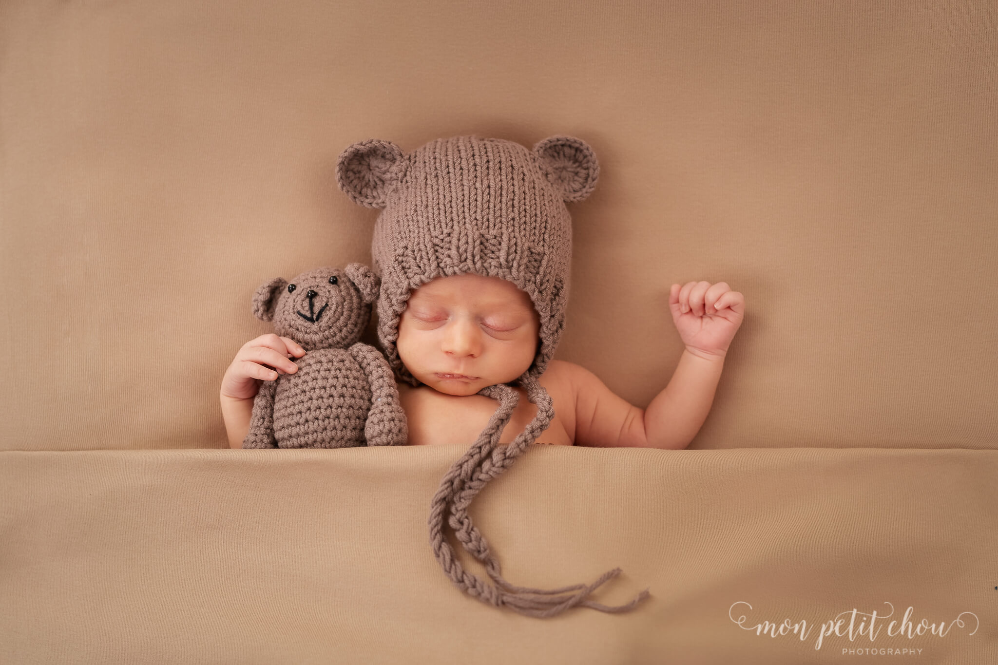 Baby boy hugging a knitted teddy wearing a bonnet with ears.