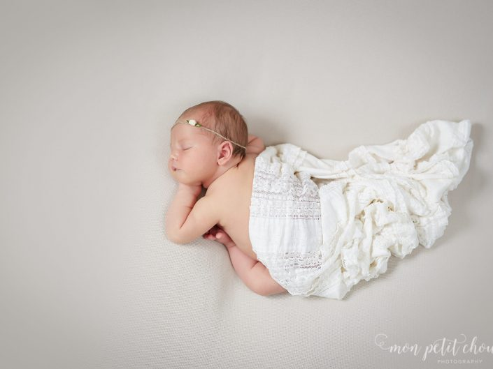Newborn girl covered in white blanket with headband