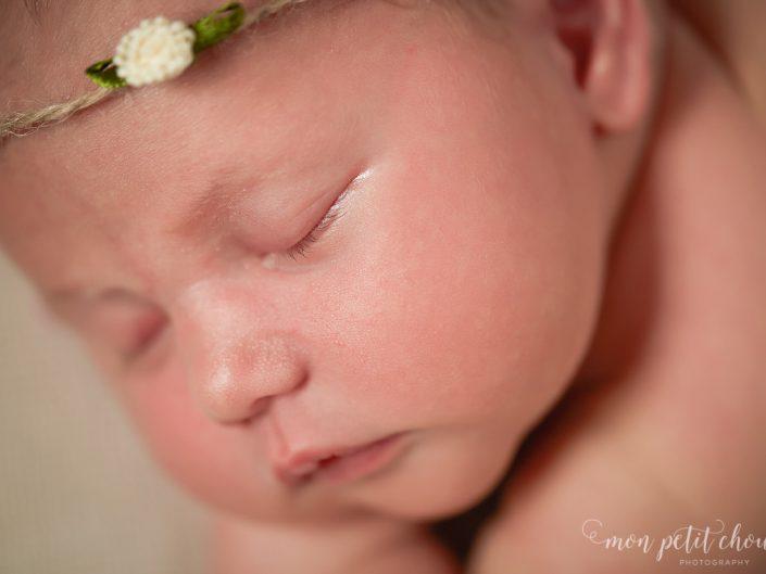 Macro shot of newborn baby girl wearing headband.