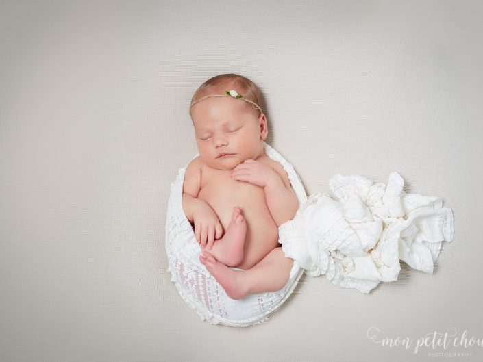 Top down shot of newborn baby girl wrapped in white blanket