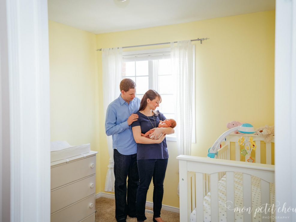 Parents holding newborn baby girl in brightly lit nursery with yellow walls