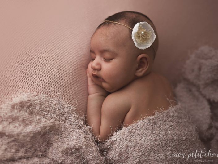 Newborn baby girl on pink fabric covered by blanket.