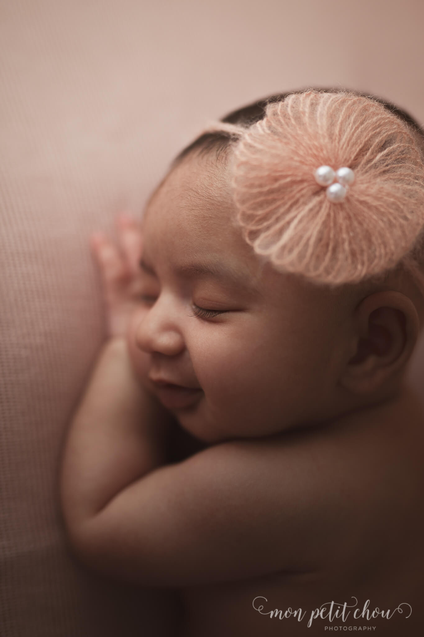 Picture of smiling newborn girl with a little flower on her head.