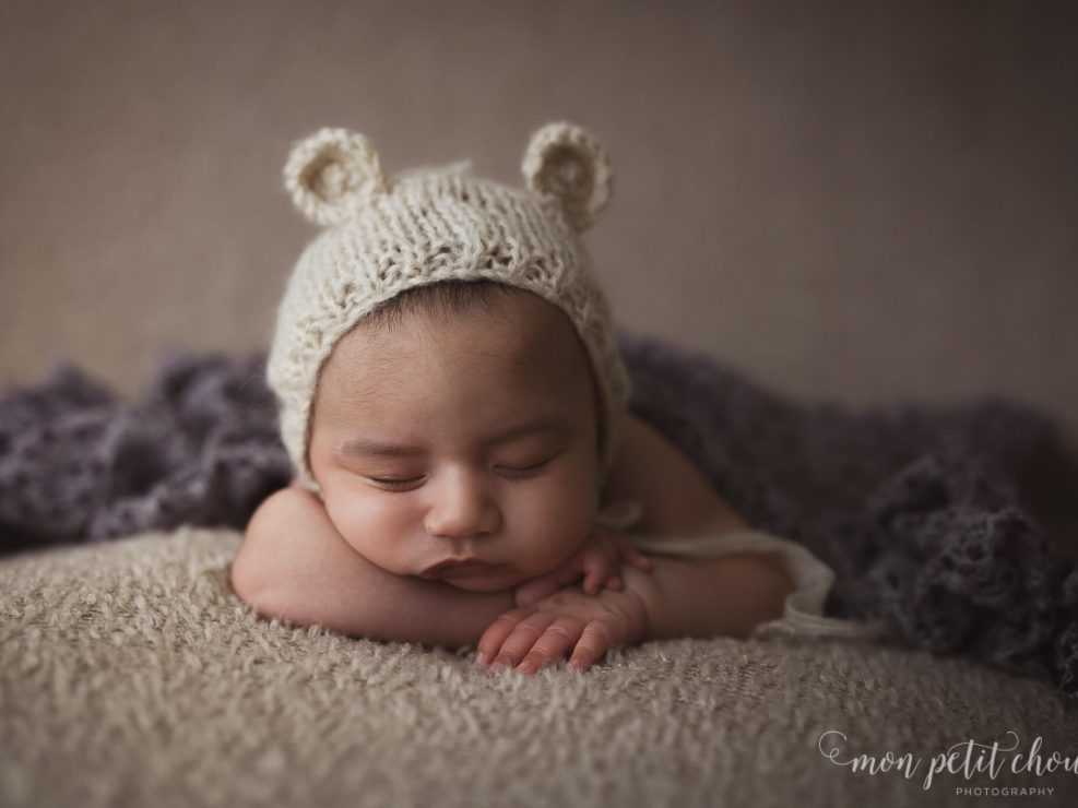 Newborn baby girl with a little bear hat covered with purple blanket.
