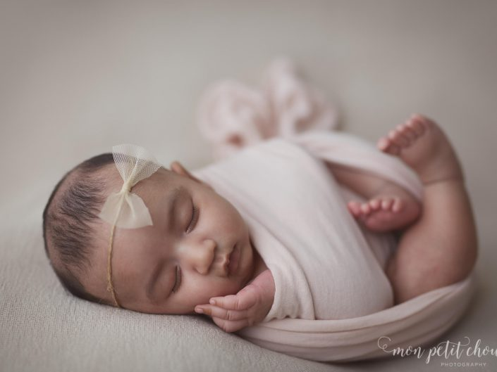 Wrapped newborn baby girl with a bow tie headband
