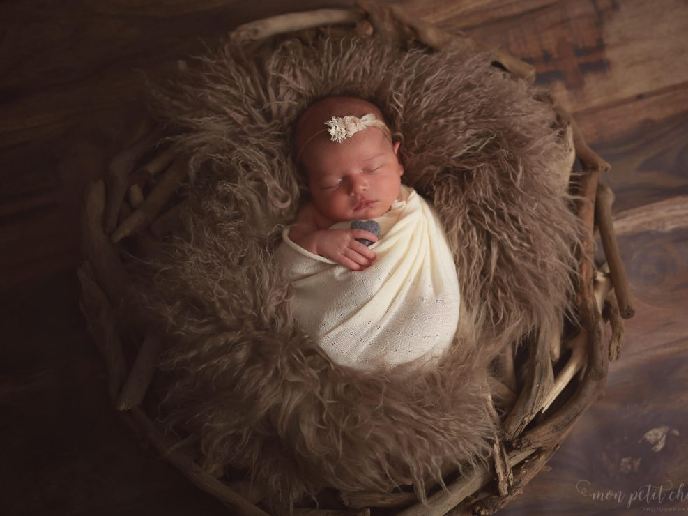 Baby girl lying on fur with a driftwood prop on wooden floow with heart in hand
