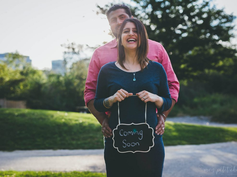"Pregnant mom holding a ""coming soon"" sign with her husband"