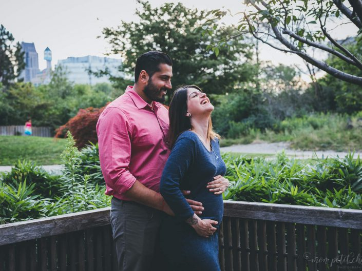Husband and wife hugging and laughing during maternity shoot at Kariya Park in Toronto