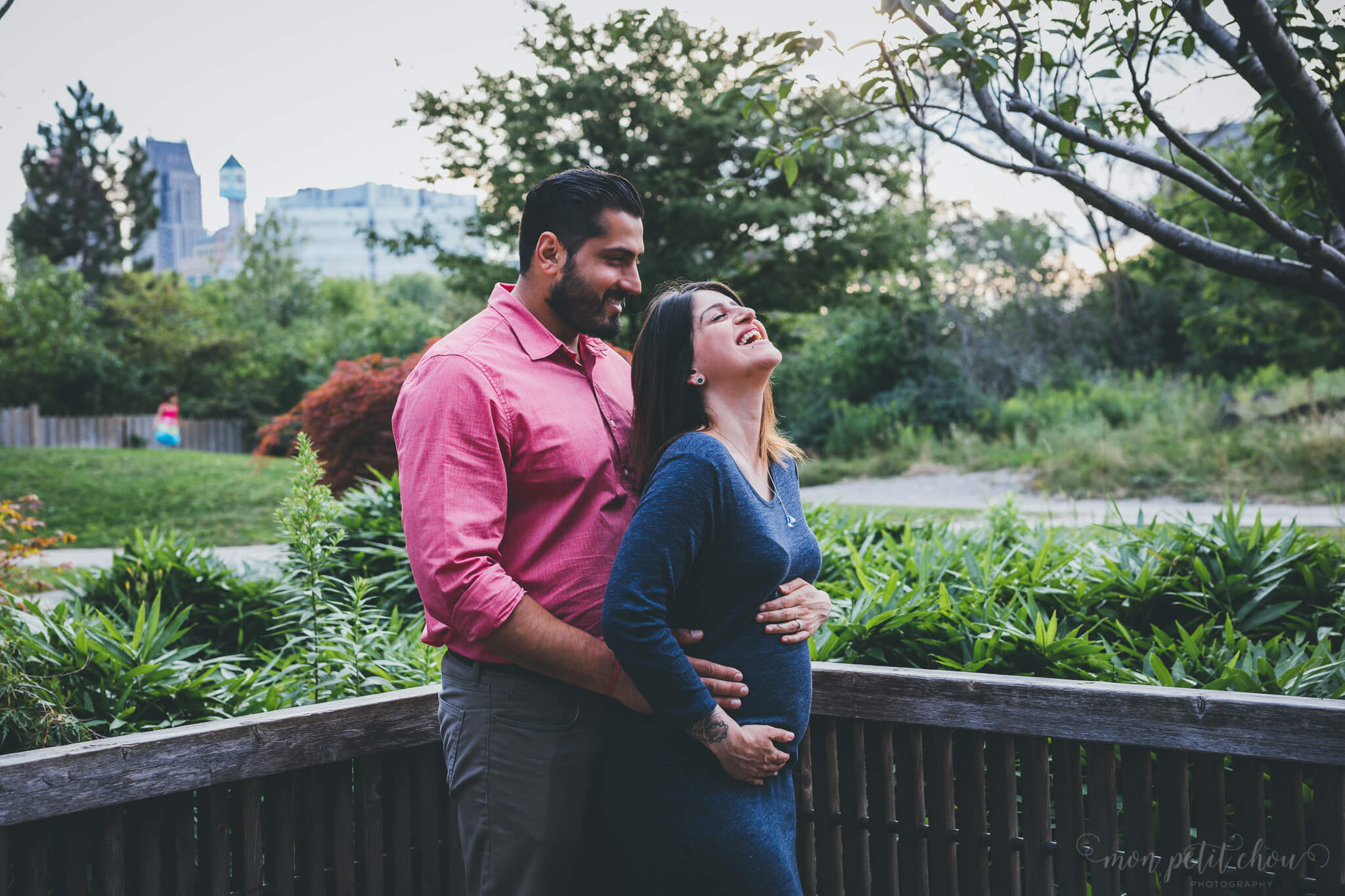 Husband and wife hugging and laughing during maternity shoot at Kariya Park in Toronto
