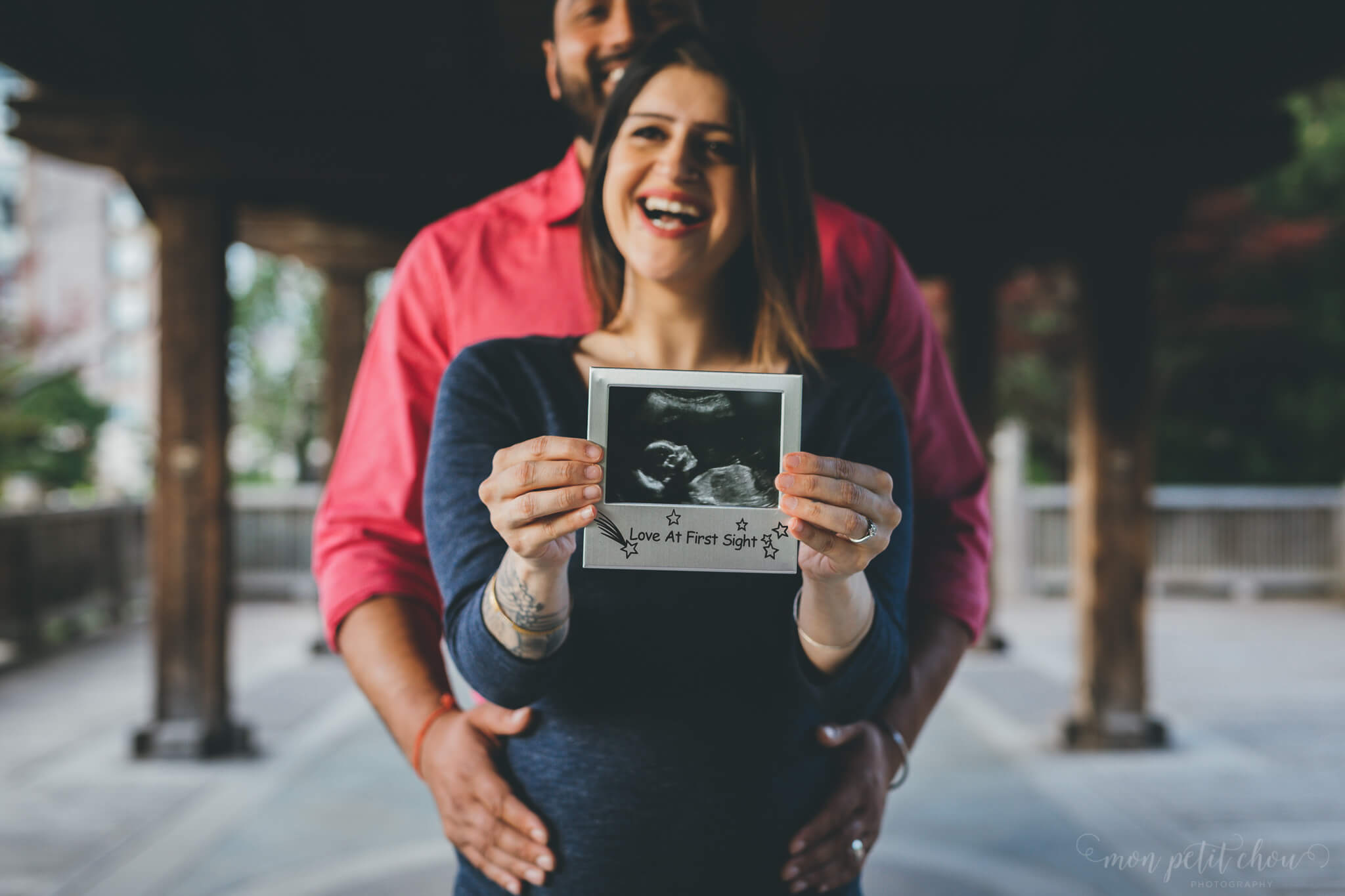 Pregnant lady holding an ultrasound picture during a maternity portrait shoot in Kariya Park Toronto