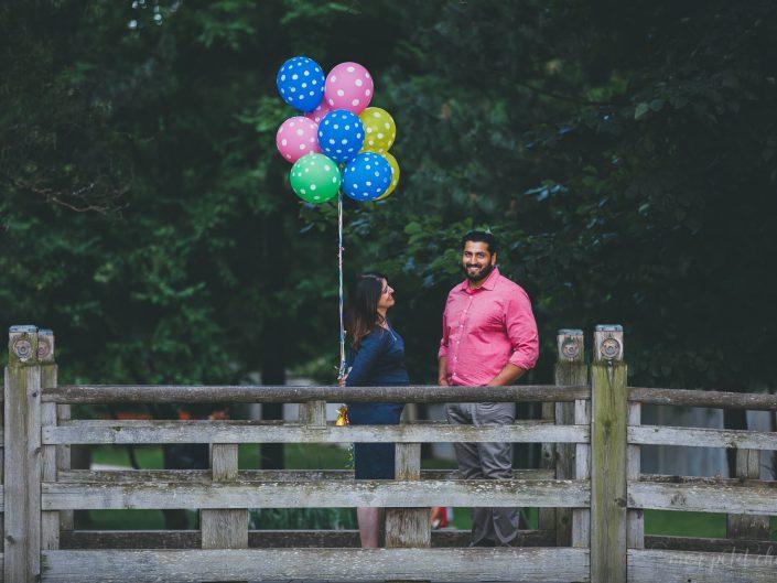 Pregnant mom holding balloons on a bridge in Kariya Park in Toronto