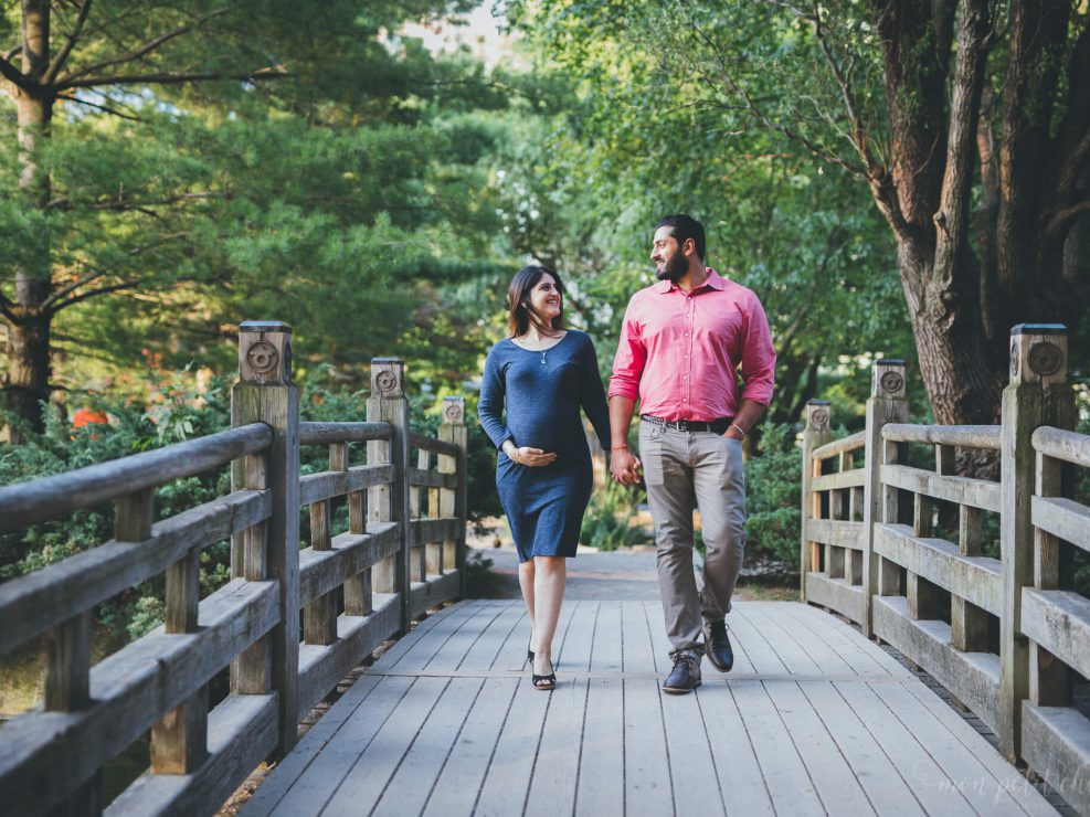 Pregnant mom holding her baby bump and walking across a bridge with her husband in Kariya Park Toronto