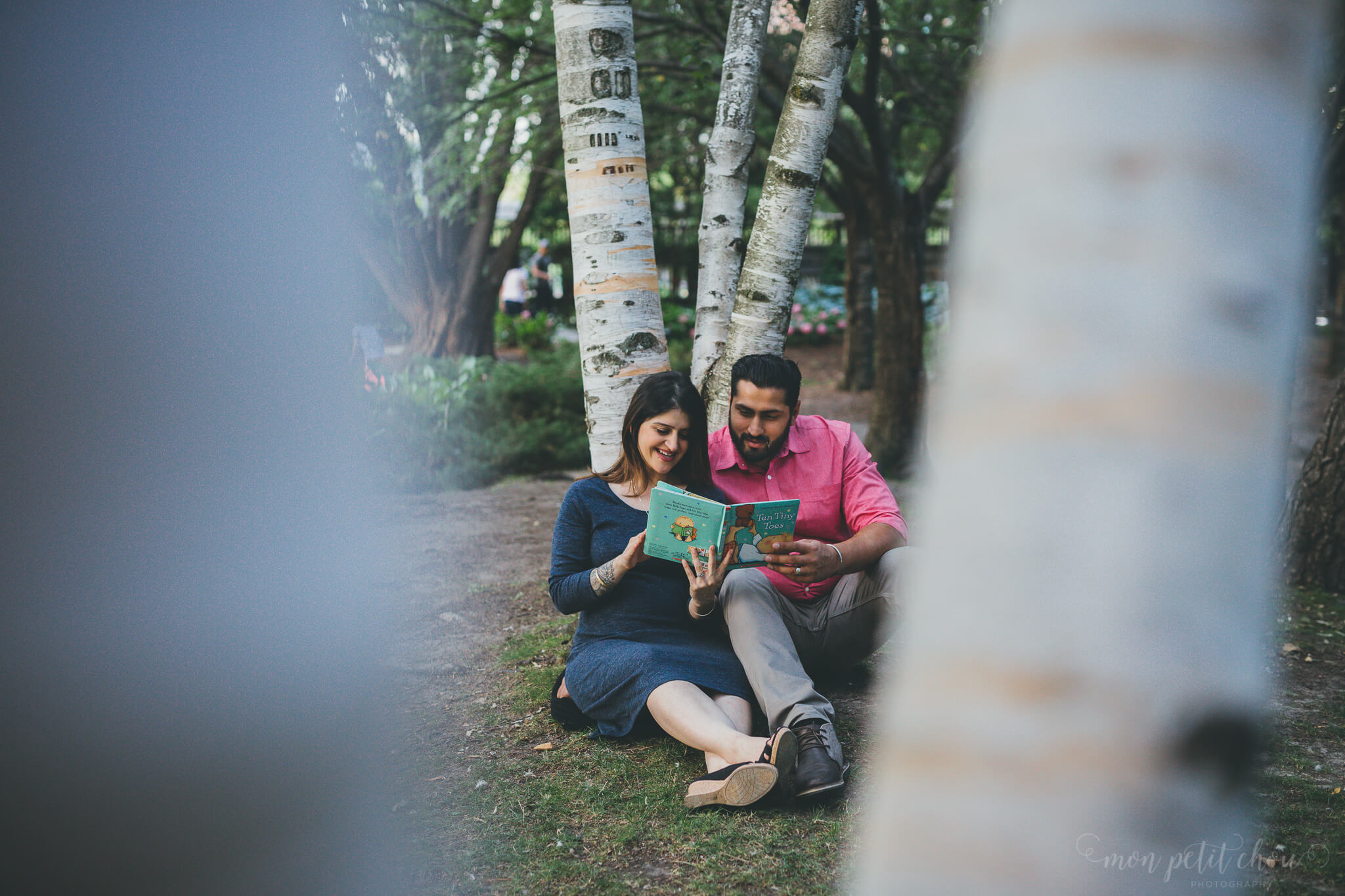Mom and dad to be reading a children's book in Kariya Park in Toronto during a maternity photo session.