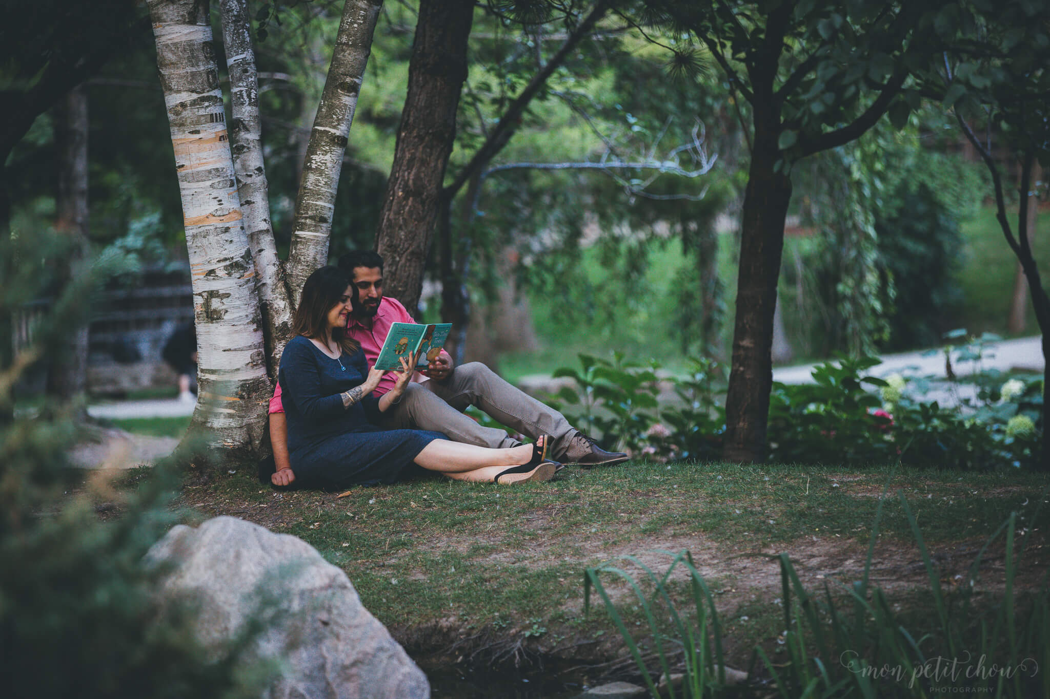 Mom and dad sitting in Kariya Park in Toronto reading a children's book during a maternity photo shoot.