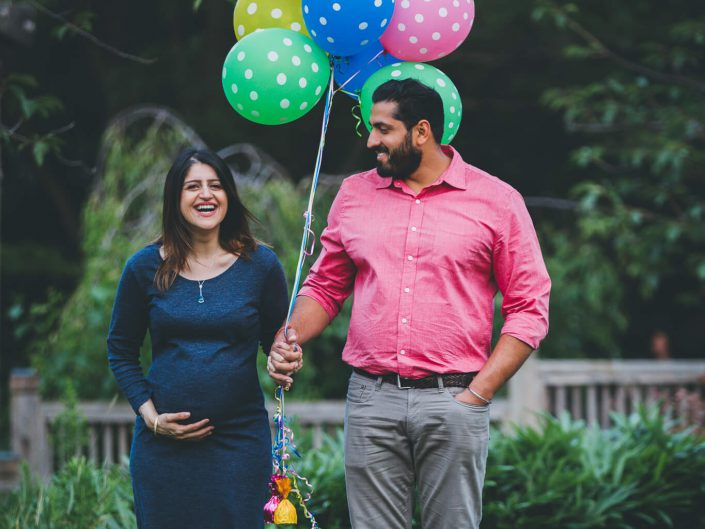 Pregnant mom to be hold ballons and laughing during a maternity shoot in Kariya Park in Toronto