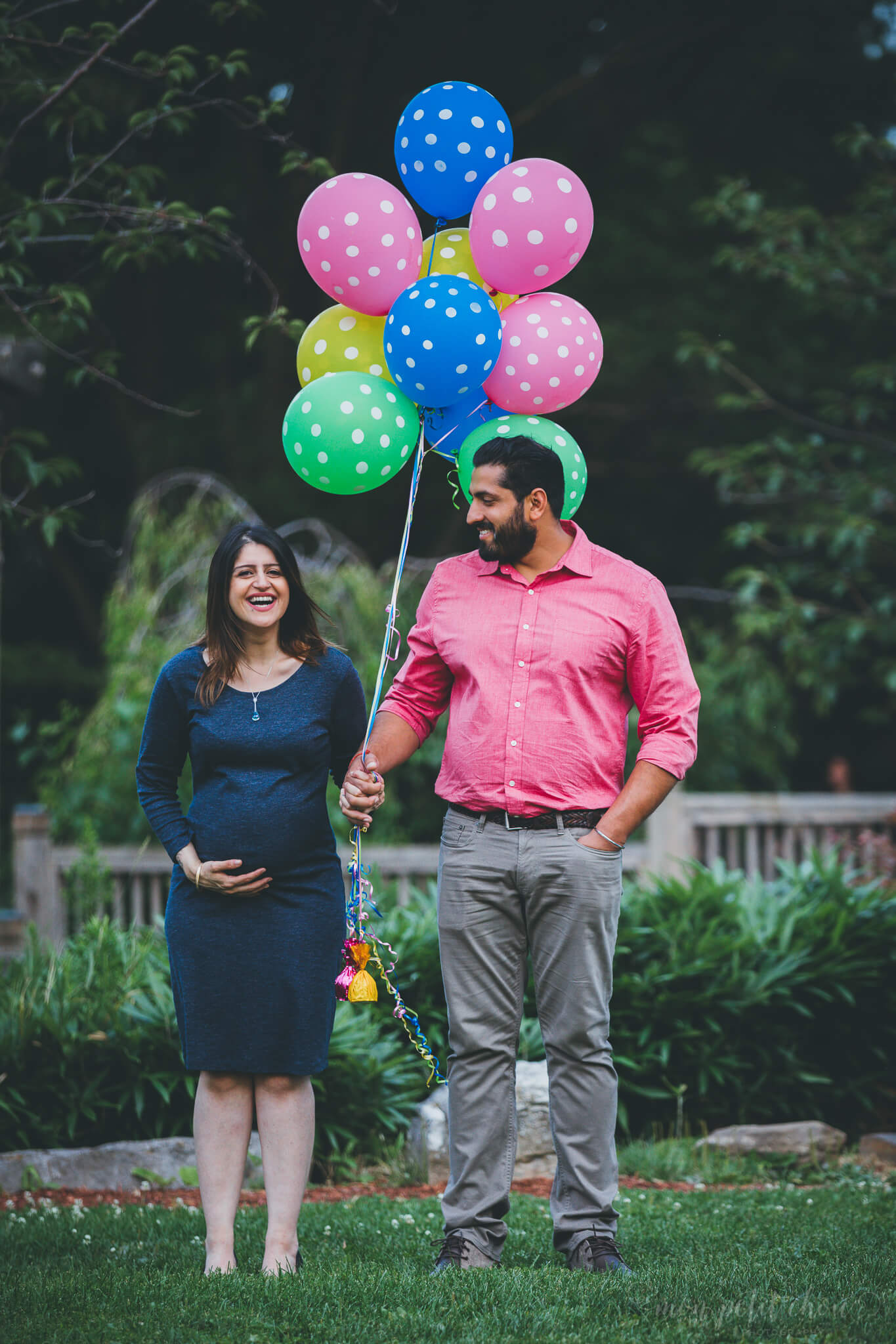Pregnany mom to be hold ballons and laughing during a maternity shoot in Kariya Park in Toronto