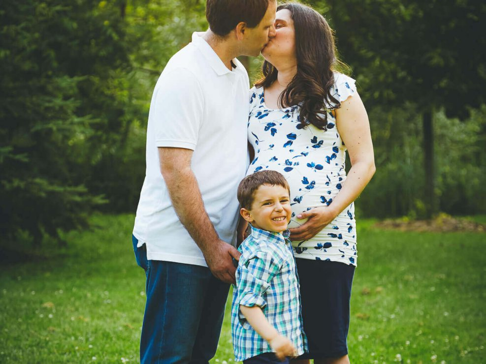 Pregnant mom and dad kissing in the park in Bolton, Ontario with their son looking on.
