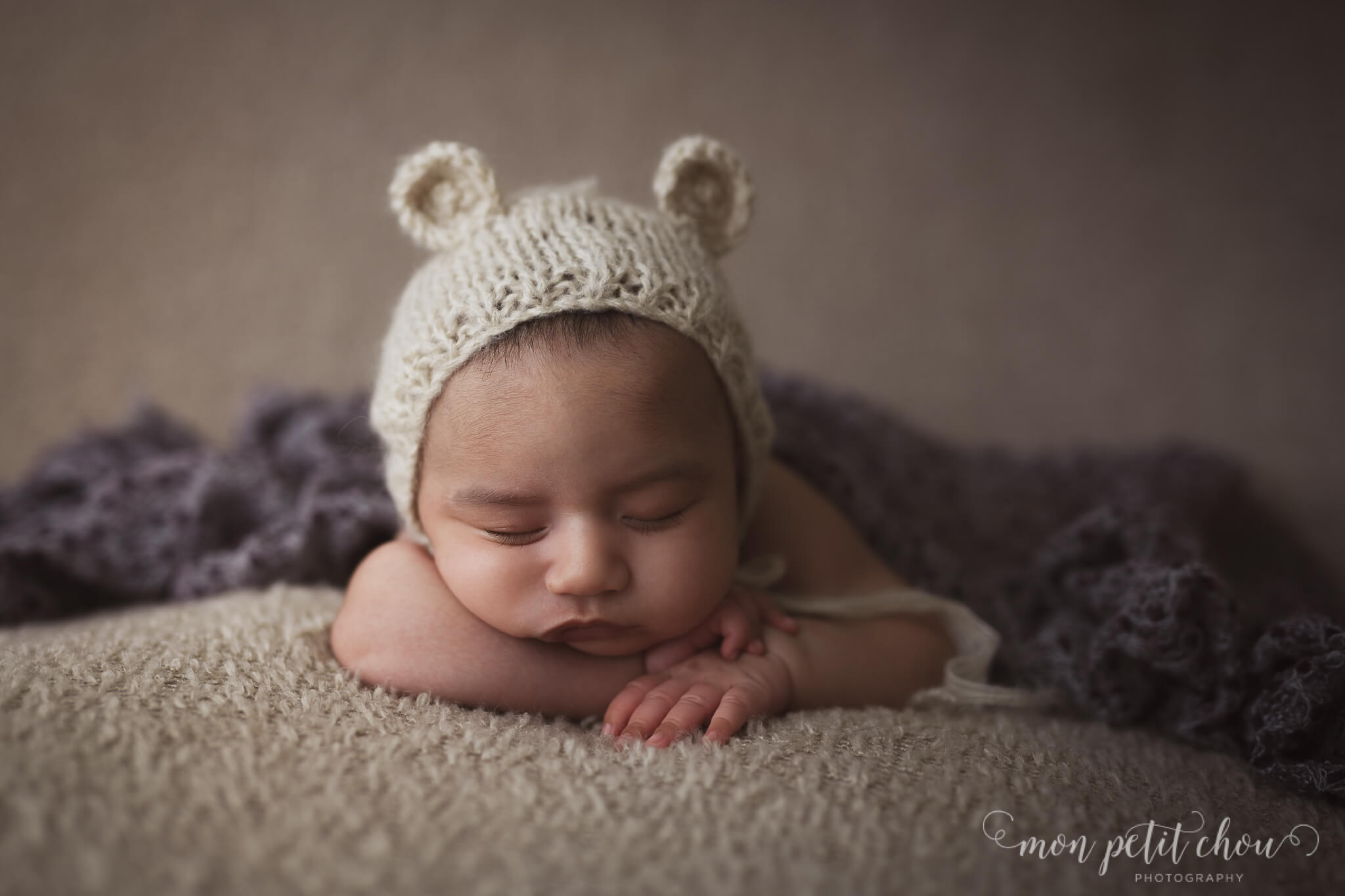 Pretty newborn baby girl in a bunny hat covered by a blanket.