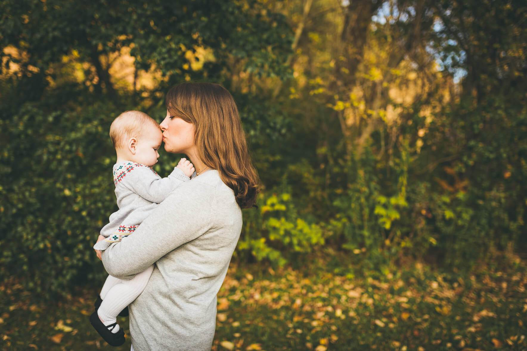 Mom kissing baby on the forehead during a fall photo shoot in Oakville
