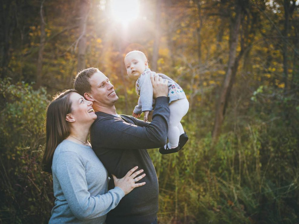 Dad lifting baby against the sunlight in Lions Valley Park during a family photography session.