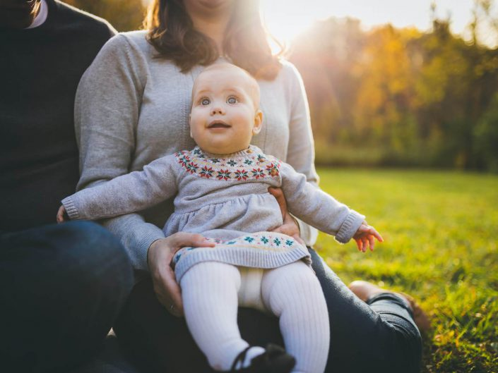 Baby laughing while sitting with parents on the grass during fall photo shoot in Lions Valley Park in Oakville.