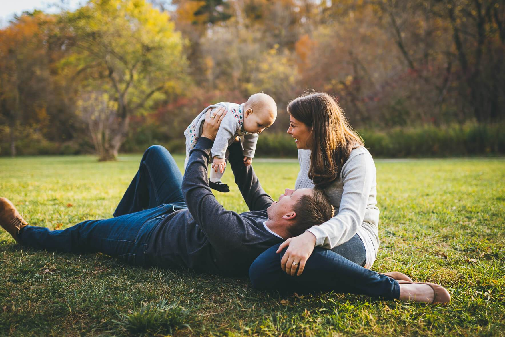 Dad lifts baby in Lions Valley Park during a fall photo shoot