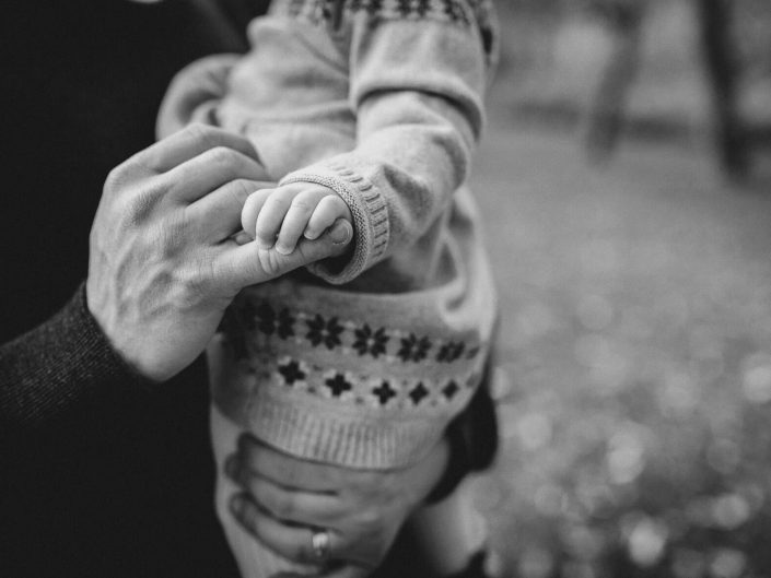 Black and white photo of baby girl holding dad's hands in Lions Valley Park.