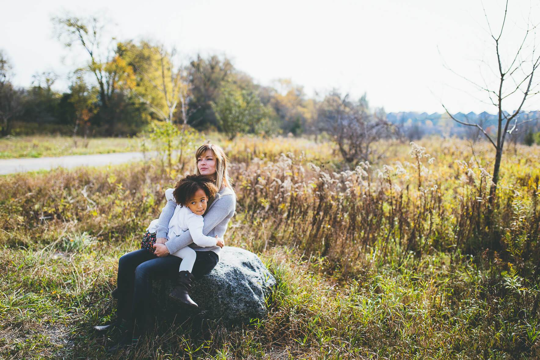 Mom sitting on a rock in a field and hugging her daughter