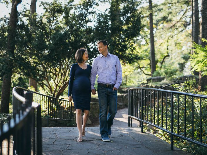 Lady and husband holding hands and smiling at each other during maternity photos session