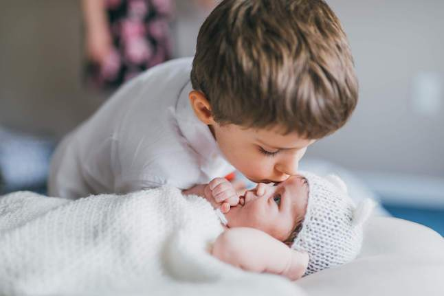 Brother kissing his baby sister