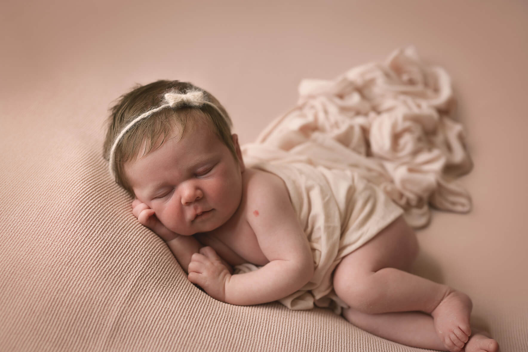 Baby lying on a blanket during her posed newborn photography shoot