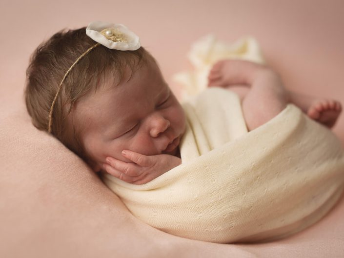 Baby with flower in her hair curled up