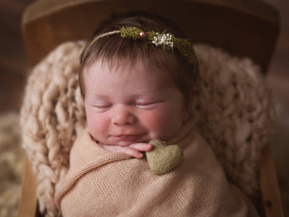 Newborn baby girl smiling in a little bed all covered up with blankets