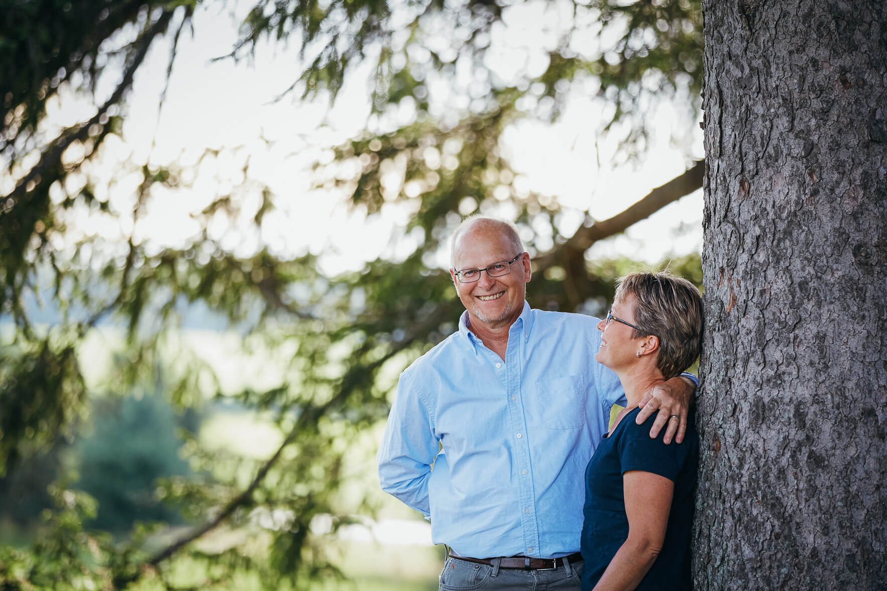 Couple smiling at camera and leaning against a tree in a park during an anniversary photo shoot in Kitchener