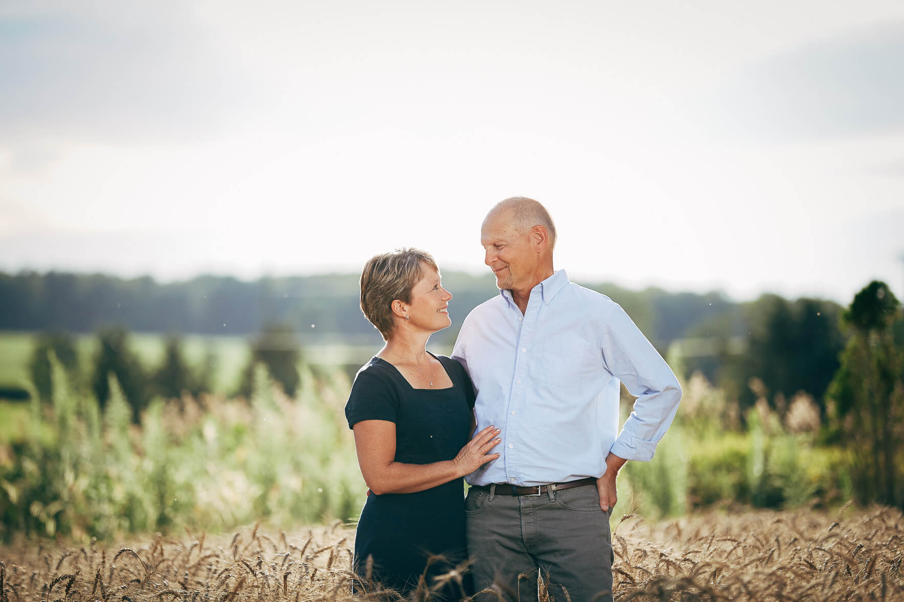 Husband and wife standing in a field of wheat in a backlit photo